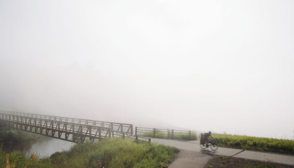 Ben Weaver riders through the fog of lake superior on his bike