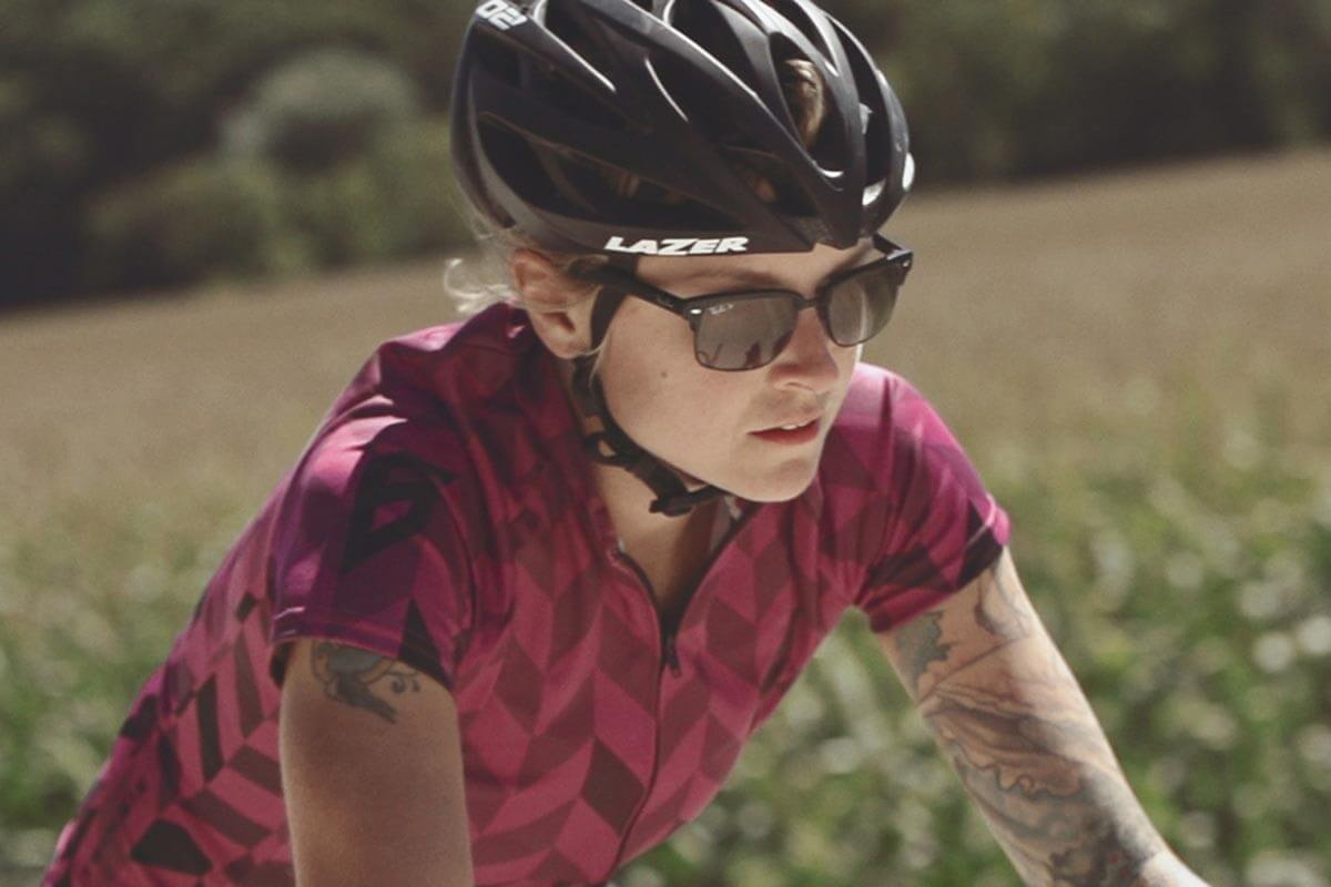 Close-up of female bike rider on gravel road