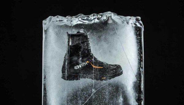 Winter cycling boot Wolvhammer sits against a black background in a block of ice