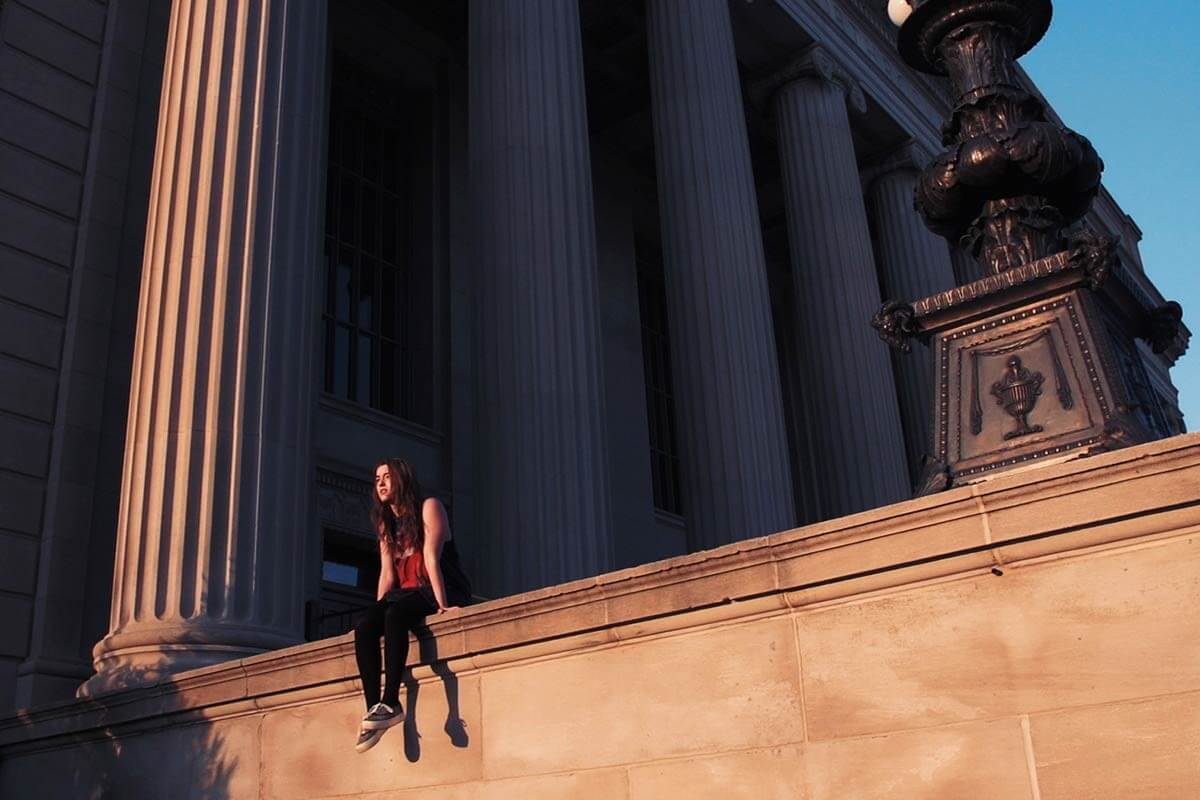 Woman sitting on ledge under pillar during sunset hour